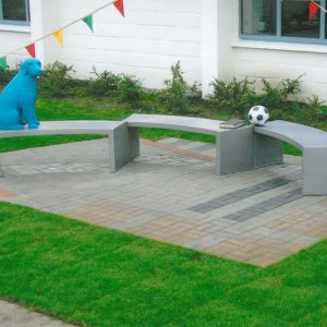 Long three tiered bench for kids but a dog, football and book sculpture.