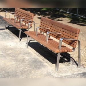 Two wooden benches with steel legs and arm rests