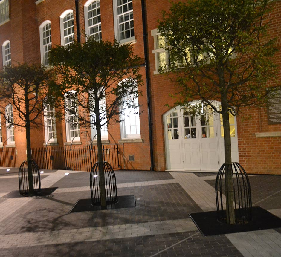 Three bird cage tree surrounds outside a red brick building