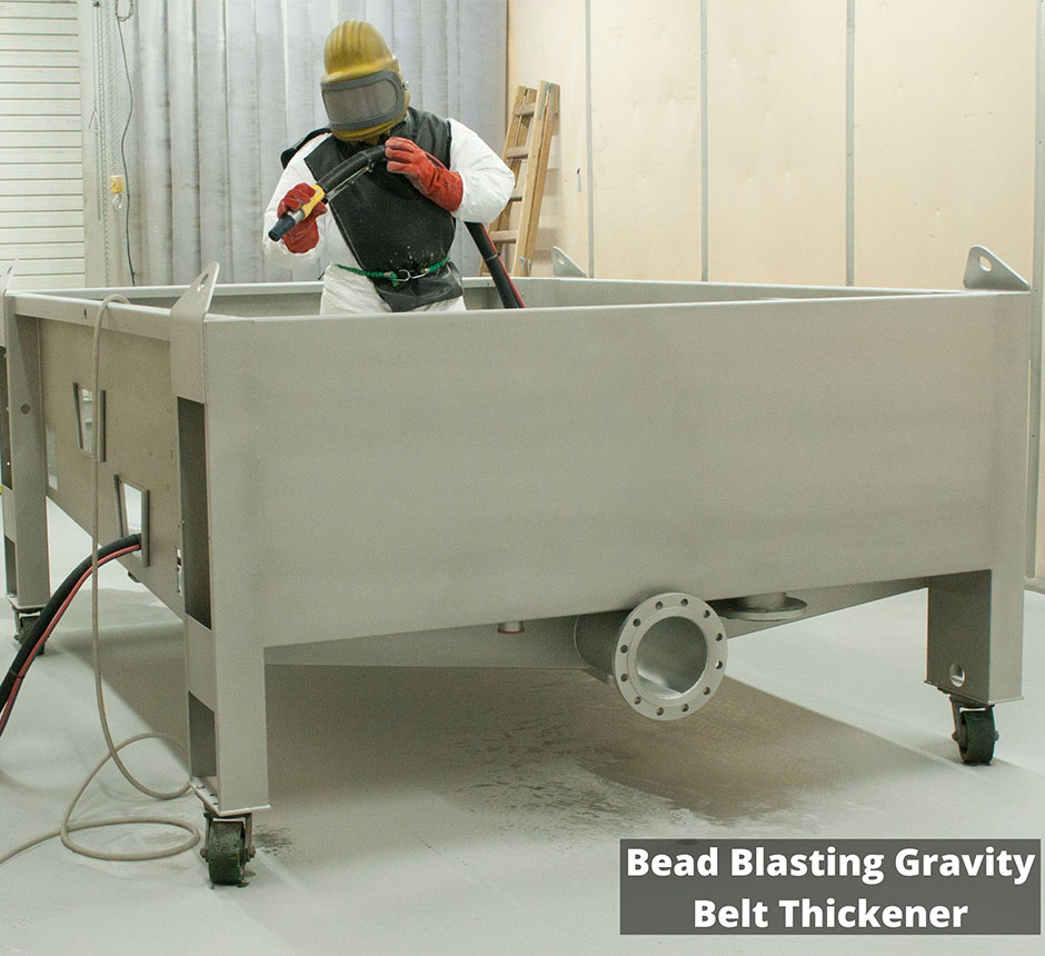 Factory worker Bead Blasting a Gravity Belt Thickner